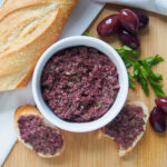 dish of tapenade with olives to one side and bread to other