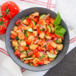 bowl of panzanella salad from overhead with tomatoes to side of bowl