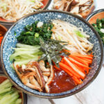 bowl of vegetarian bibimbap with the various vegetables in piles over the rice underneath