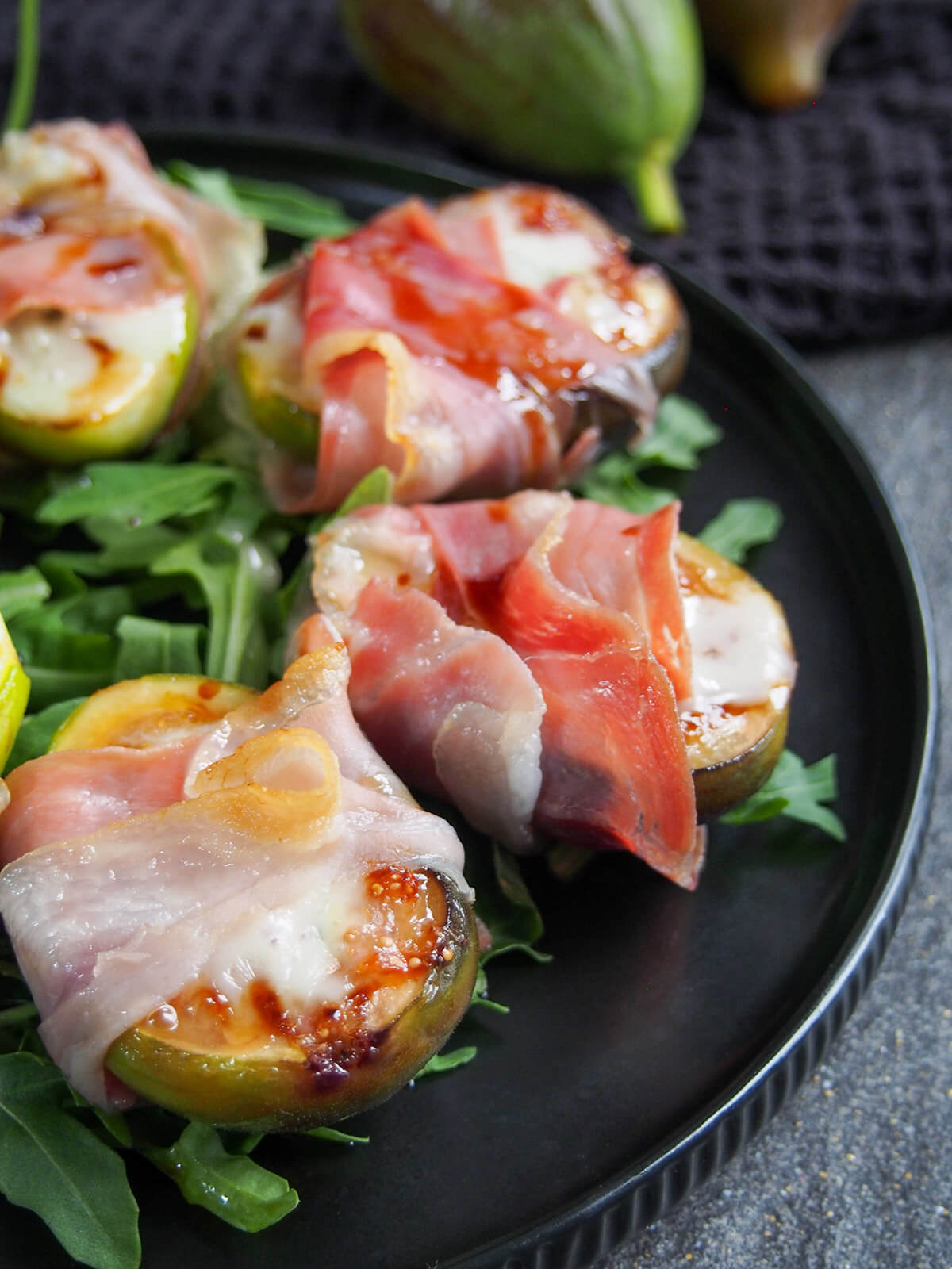 side view of prosciutto wrapped figs on black plate