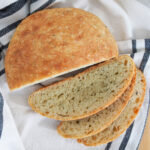 cut loaf of no knead olive oil rosemary bread from overhead with slices to bottom
